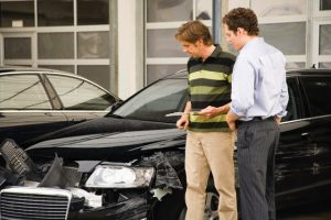 Insurance adjuster assessing damage to car --- Image by © Juice Images/Corbis